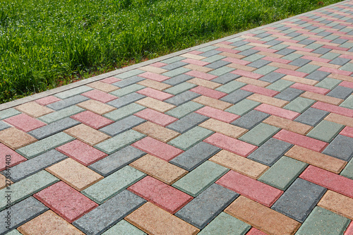 Colorful cobblestone road pavement and lawn divided by a concrete curb Canvas Print