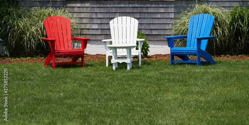 Photo red white and blue wooden adirondack chairs on a green lawn in front of a house