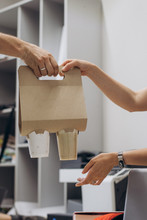 The Hand Of The Courier Is Served By The Owner With Drinks For Office Workers Who Have Ordered The Delivery Of Coffee To The Office. Coffee Take Away Order Online Delivery Concept