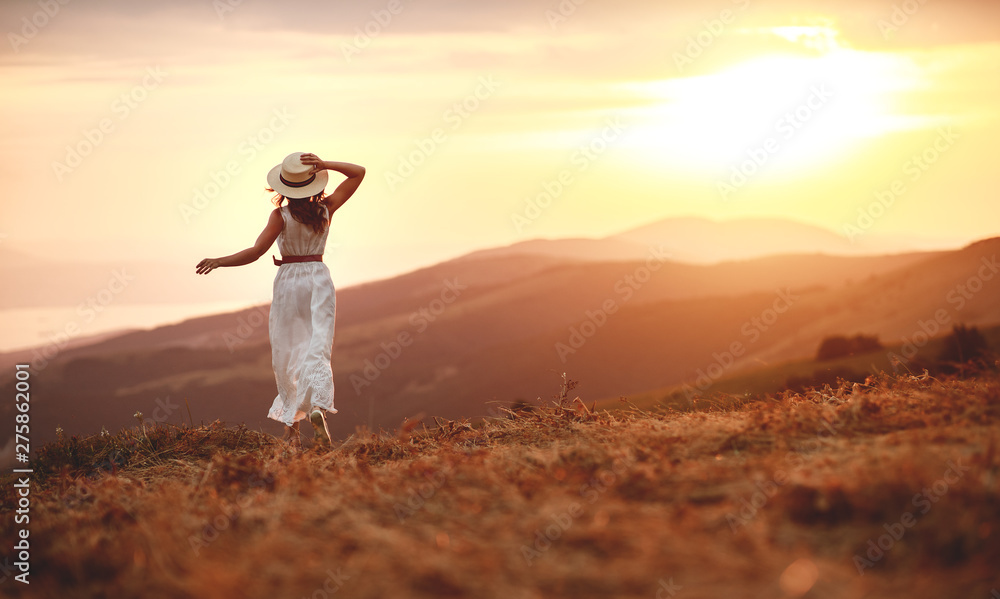 Fototapety, obrazy: Happy woman standing with her back on sunset in nature iwith open hands
