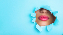 Plump Pink Lips Peep Into Slit Of Blue Paper