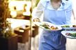 Bedienung serviert Essen für die Gäste im Restaurant
