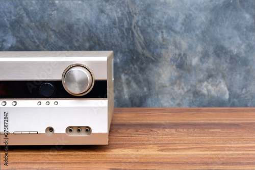 Half front side AV receiver with volume and AUX Plugin on wood table Canvas Print