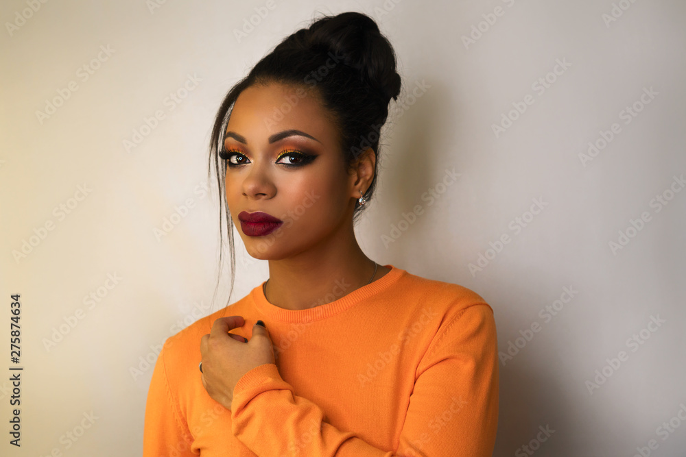 Fototapety, obrazy: Portrait of attractive afro american young woman with fashion luxury makeup orange-coloured shades and her hair scraped back into high bun. Perfect Skin. Long eyelashes. Pouty lips. Beauty industry.