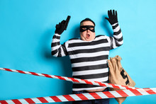 Scared Surprised Thief Has Been Cought By Witness. Close Up Portrait. Isolated Blue Background. Studio Shot