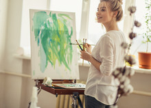 Happy Blond Girl Having A Rest While Painting In The Light Modern Room, Close Up Side View Photo. Dauber
