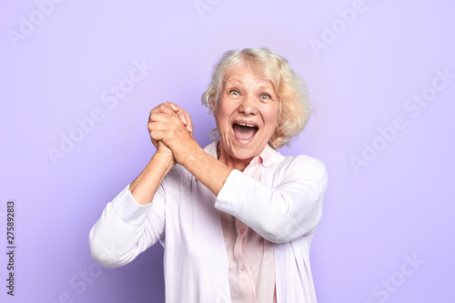 Old blonde woman keeping hands, palms together , rejoicing at good news, winning of favourite team, light blue background Canvas-taulu