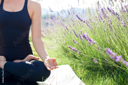 Fotobehang Ontspanning Woman is practicing yoga in lavender field. Girl is meditating, sitting in lotus pose outdoors. Sport workout at nature. Concept of healthy lifestyle, wellbeing. Female fitness classes. Close up