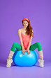 canvas print picture - woman with long red curly hair, green eyes and freckles, sits on fit ball spreading legs wide apart ready to start aerobics training, hands on ball, dressed in stylish pink bodysuit, green leggins