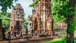 Leinwandbild Motiv Only intact ancient Buddha statue among the destroyed statues in Ayutthaya historical park, Thailand.