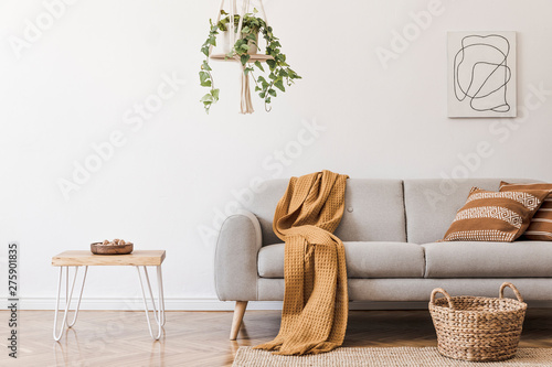 Valokuva  Modern boho interior of living room at cozy apartment with gray sofa, honey yellow pillows and plaid, plants, paintings, rattan basket and design personal accessories