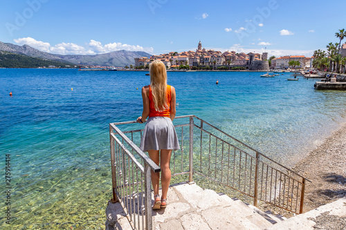 Fototapeta A girl standing at the viewpoint of the old town in Korcula