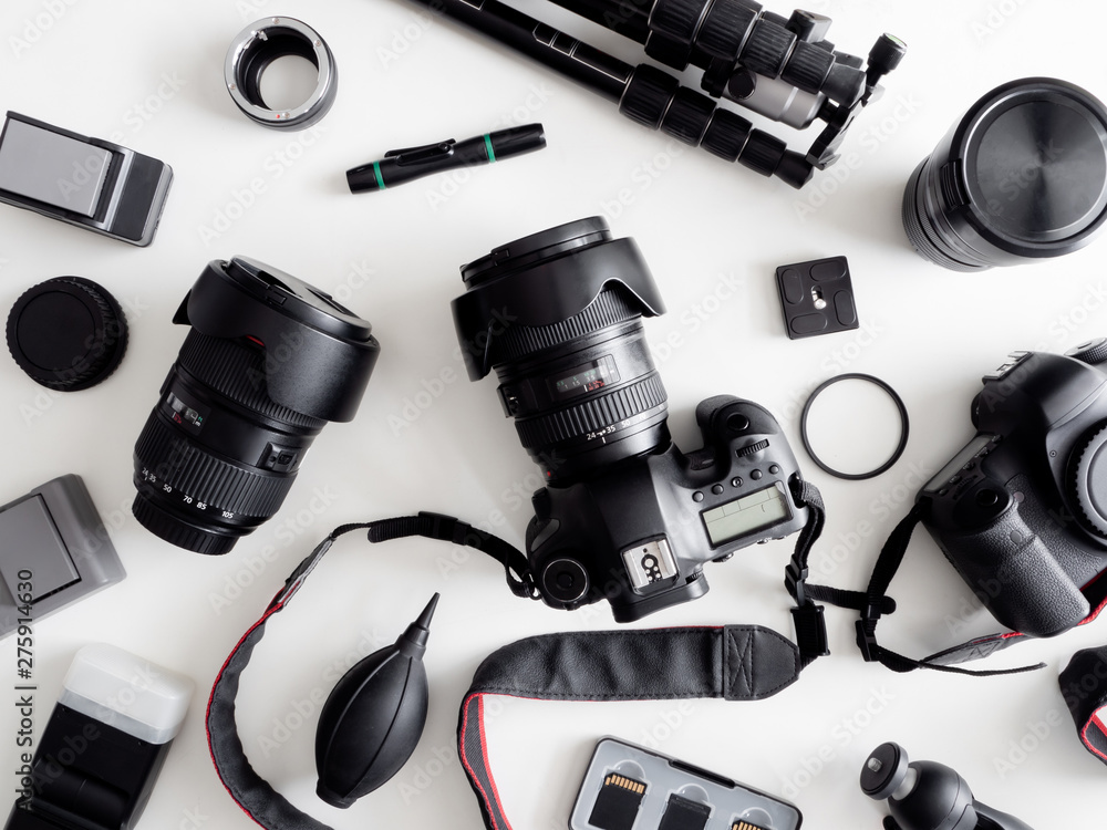 Fototapety, obrazy: top view of work space photographer with digital camera, flash, cleaning kit, memory card, tripod and camera accessory on white table background