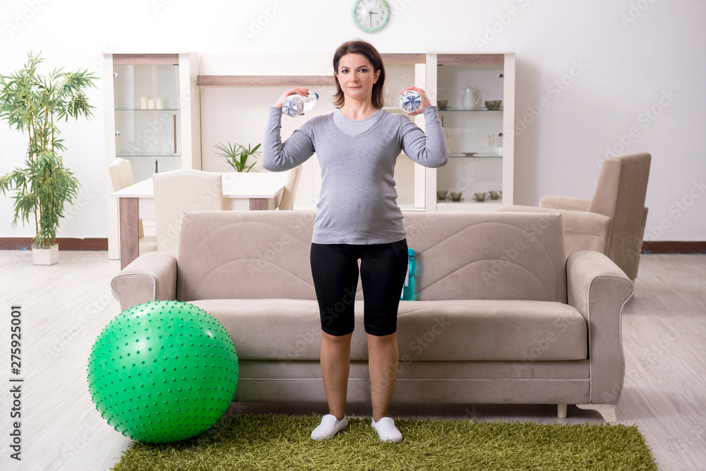 Fototapety, obrazy: Aged pregnant woman doing exercises at home