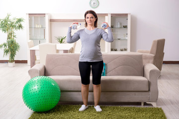 Aged pregnant woman doing exercises at home
