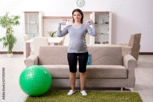 plakat Aged pregnant woman doing exercises at home