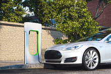 Electric White Modern Car Near Electric Car Charging Station At Street. 3d Rendering