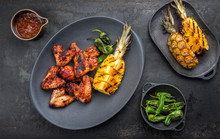 Exotically Barbecue Chicken Wings With Hot Chili Sauce, Jalapeno And Pineapple As Top View On A Cast Iron Plate