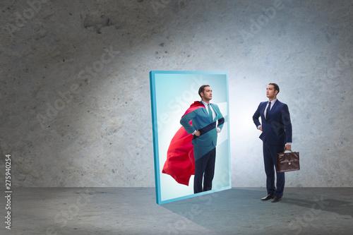 Fotografía  Businessman seeing himself in mirror as superhero