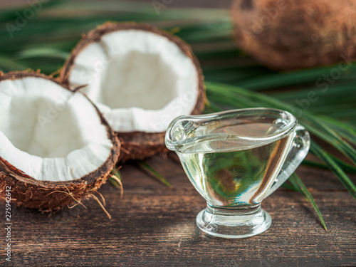 Fototapeta Liquid coconut MCT oil and halved coco-nut on wooden table. Health Benefits of MCT Oil. MCT or medium-chain triglycerides, form of saturated fatty acid. obraz