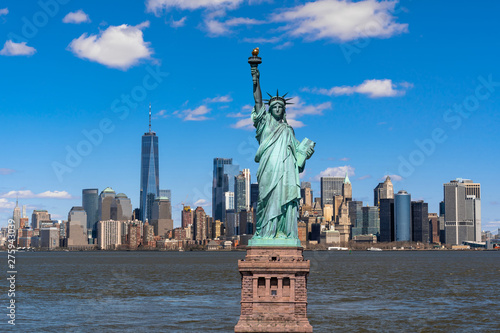 Photo Stands New York The Statue of Liberty over the Scene of New york cityscape river side which location is lower manhattan,Architecture and building with tourist concept