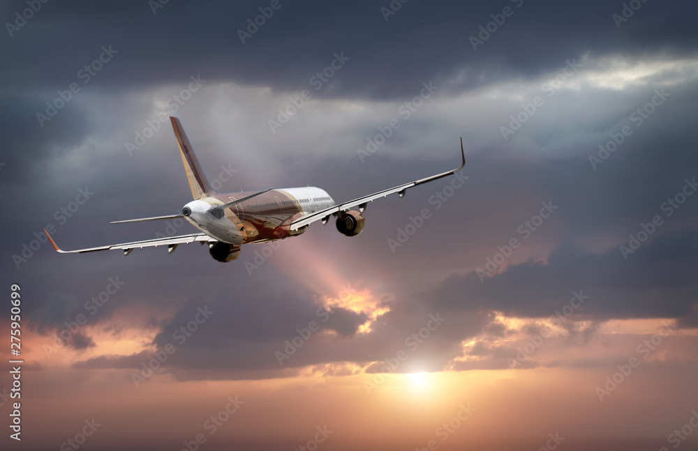 Fototapety, obrazy: passenger plane flying in the stormy dramatic sky. the sun shines from behind the clouds. the plane flies