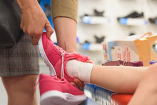 Little Girl Tries On New Shoe In Store