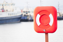 Red Ring For Water Safety At Sea Dock And Ships In Background