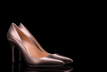 Elegant Female Shoes Close Up. A Pair Of Bronze Shoes On A Black Background With Copy Space. Beautiful High-heeled Shoes. Women's Shoes On A Black Background.