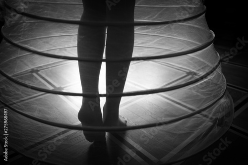 Fotografía Bare feet of a woman in a crinoline under the beam of light, black and white sho