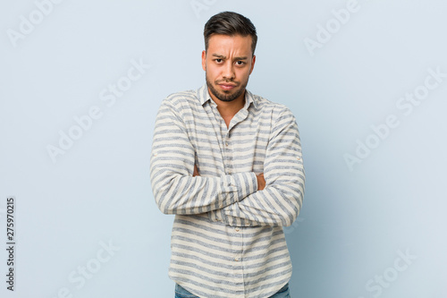 Fotografiet  Young handsome filipino man frowning face in displeasure, keeps arms folded