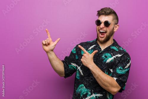 Pinturas sobre lienzo  Young man wearing a vacation look pointing with forefingers to a copy space, expressing excitement and desire
