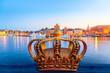 Leinwanddruck Bild Golden crown on Skeppsholm bridge with illuminated Stockholm old city center Gamla Stan in the background during twilight sunset.