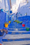 Fototapeta Na drzwi - Small narrow blue streets with colorful pots line, Chefchaouen or Chaouen, Morocco