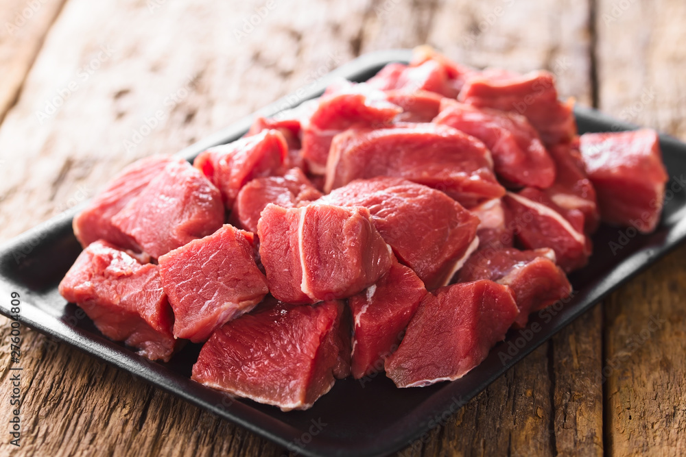 Fototapeta Fresh raw diced red beef meat on cast iron plate (Selective Focus, Focus one third into the meat)
