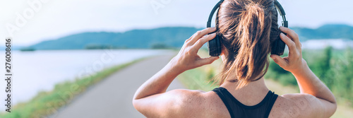 Fotografia  Young teenager girl adjusting  wireless headphones before starting jogging and listening to music