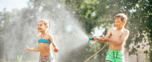 Two Childs Playing In Garden, Pours Each Other From The Hose, Makes A Rain. Happy Childhood Concept Image.