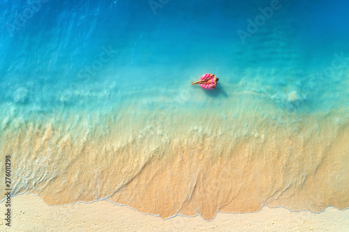 Foto auf Gartenposter Blau Jeans Aerial view of a young woman swimming with the donut swim ring in the clear blue sea with waves at sunset in summer. Tropical aerial landscape with girl, azure water, sandy beach. Top view. Travel