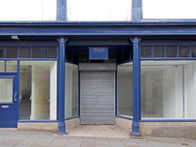 The Facade Of An Old Abandoned Shop Painted Blue And White With Empty Store Front Dirty Windows And Closed Shutters On The Door
