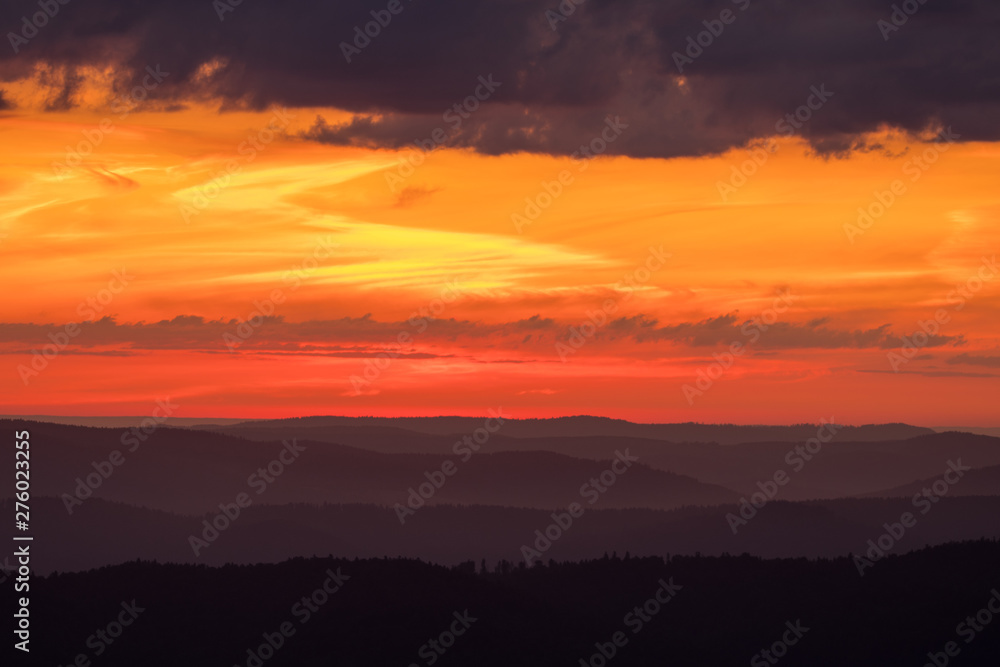 Orange sky, clouds and mountains. Beautiful sunrise in the Bieszczady mountains. Poland