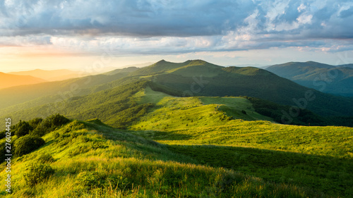 Stunning summer sunrise in the mountains. Beautiful green alpine meadow and blue sky. Polonina Wetlinska. Bieszczady. Poland