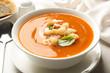 Leinwandbild Motiv Bowl of sweet potato soup with croutons and basil served on table, closeup