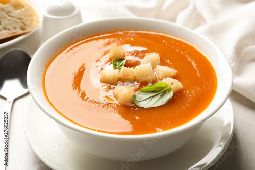 Bowl of sweet potato soup with croutons and basil served on table, closeup