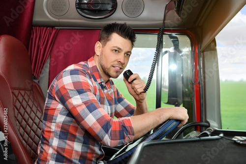 Photo Stands Akt Driver using CB radio in cab of modern truck