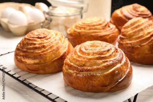 Fotografie, Obraz  Cooling rack with tasty buns on table, closeup. Fresh from oven