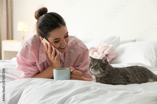 Montage in der Fensternische Individuell Young woman with cup of coffee talking on phone while lying near cute cat in bedroom. Pet and owner