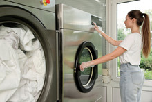 Young Woman Pressing Buttons On Washing Machine In Dry-cleaning