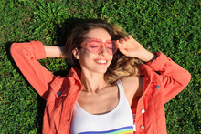 Portrait Of Happy Woman With Heart Shaped Glasses On Green Lawn, Top View