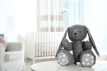 Stuffed Toy Bunny On Table In Baby Room Interior. Space For Text