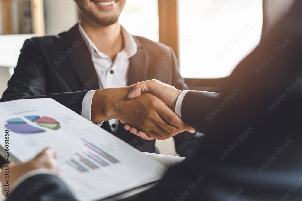 Fototapeta Banker and client shaking hands after business loan grant.